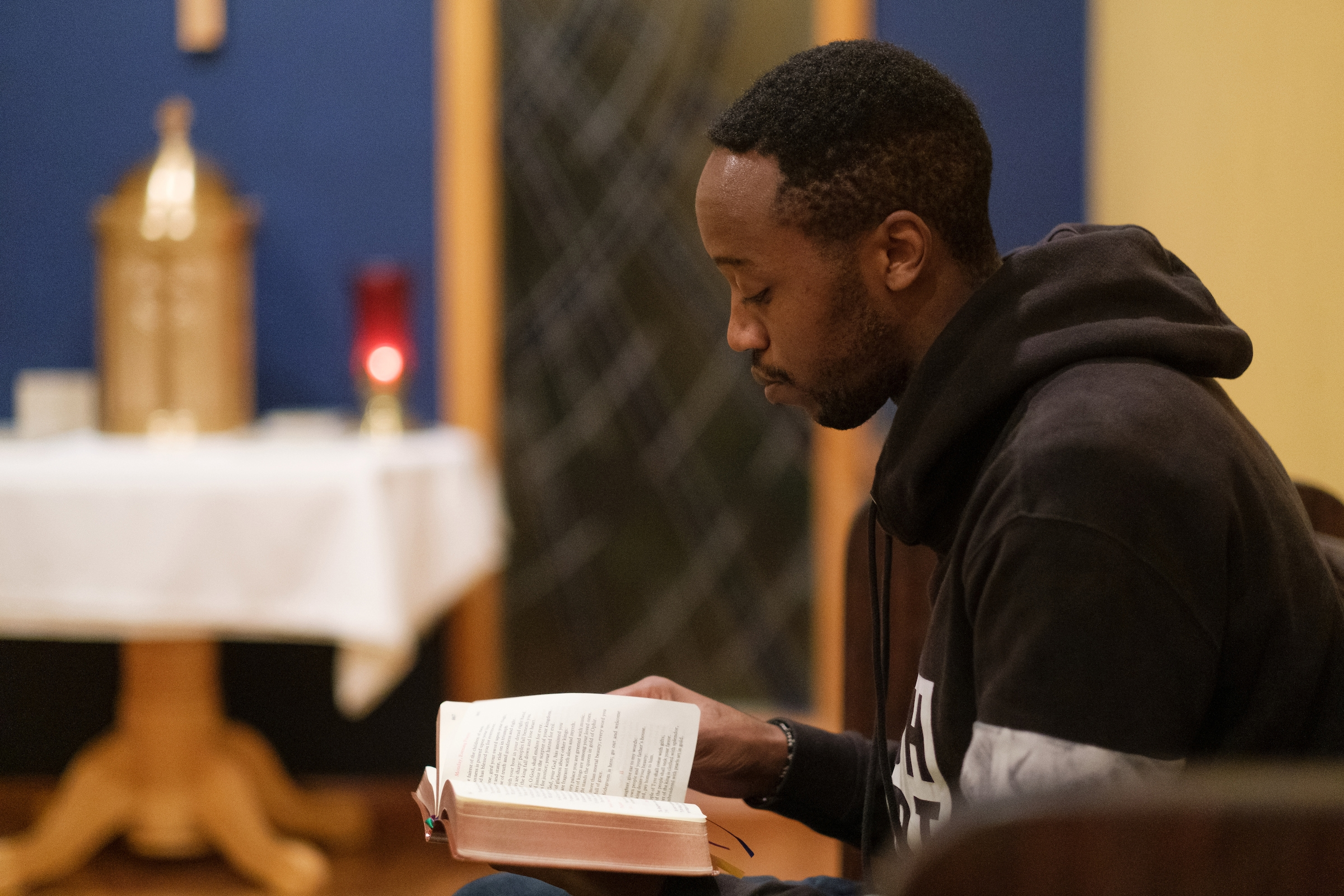 Seminarian Patrick Mbuiyu takes part in evening prayers at the Vianney House on Monday, January 21, 2019 in Seattle. (PHOTO by Stephen Brashear) Book, Chapel, Prayer
