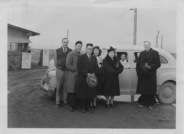 Rev. L.H. Tibesar posing with the Kinoshita family at gates of Camp Minidoka, Idaho in 1945. VR700.02282