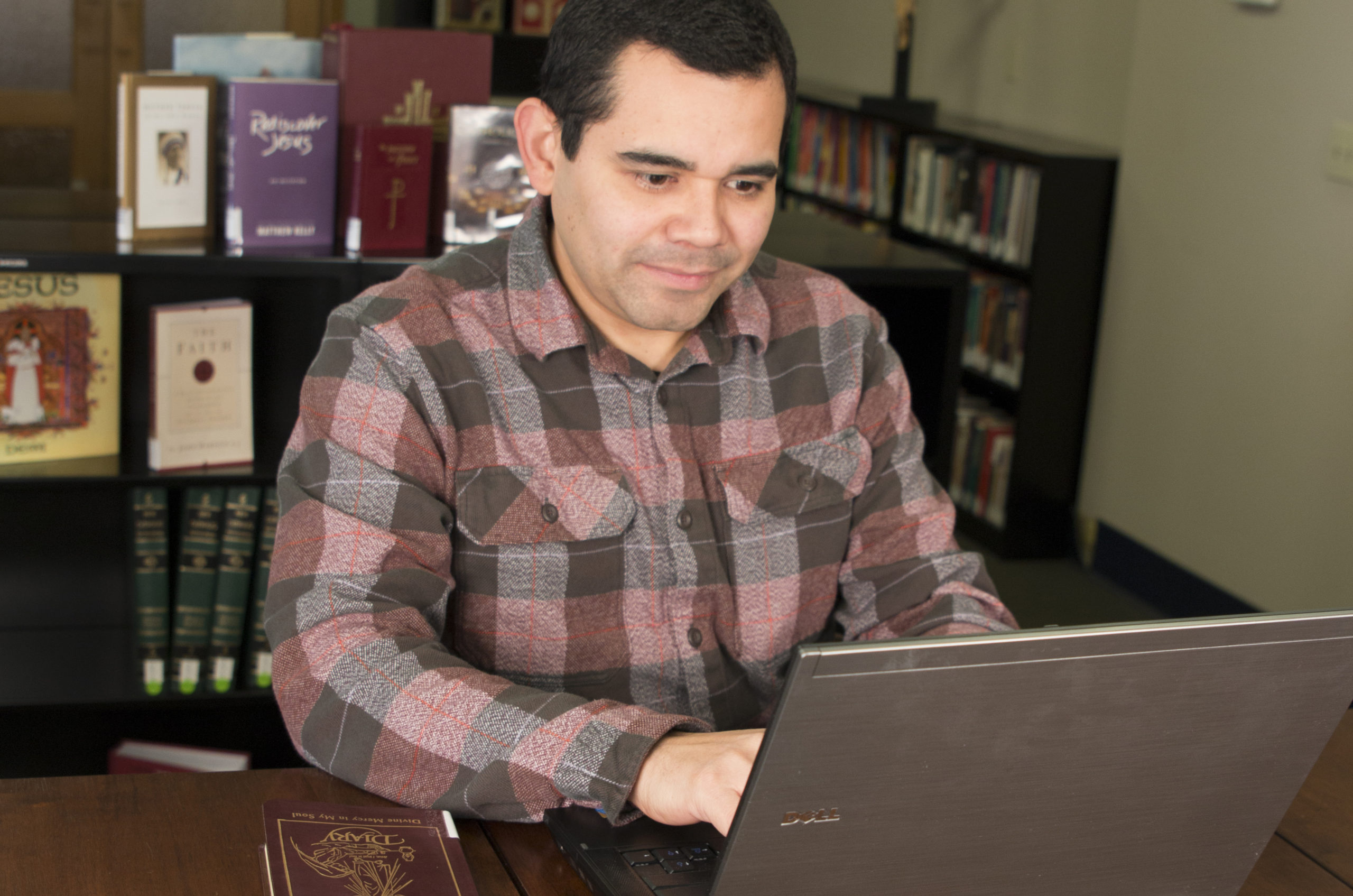 Edwin Ferrera on the computer in the Chancery Library Media Center, November 20, 2015. Books, Janis Olson Photography.