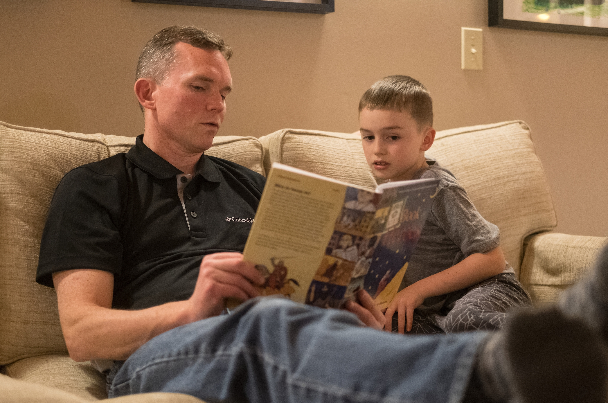 Keith Mack, left, reads from a book about saints to son Patrick before bedtime at their home on Saturday January 21, 2017 in Oak Harbor, Washington. (PHOTO by Stephen Brashear) Domestic Church, father, son, reading, book.