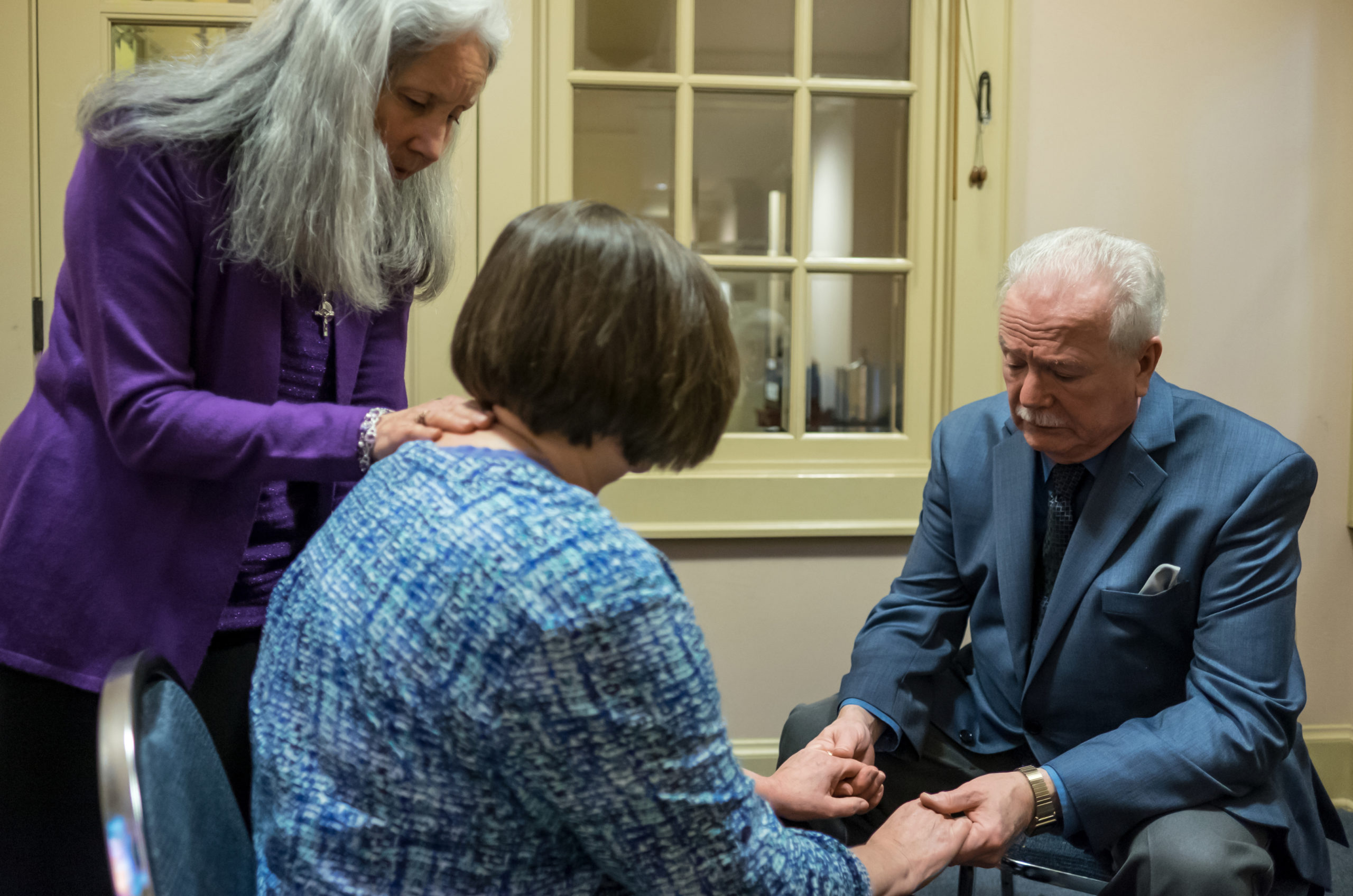 Healing Prayer Ministers John Sullivan and his wife Carmen pray with a supplicant after Mass at Our Lady of Perpetual Hope Parish Church on Sunday November 15, 2015 in Everett, Washington. (PHOTO by Stephen Brashear)