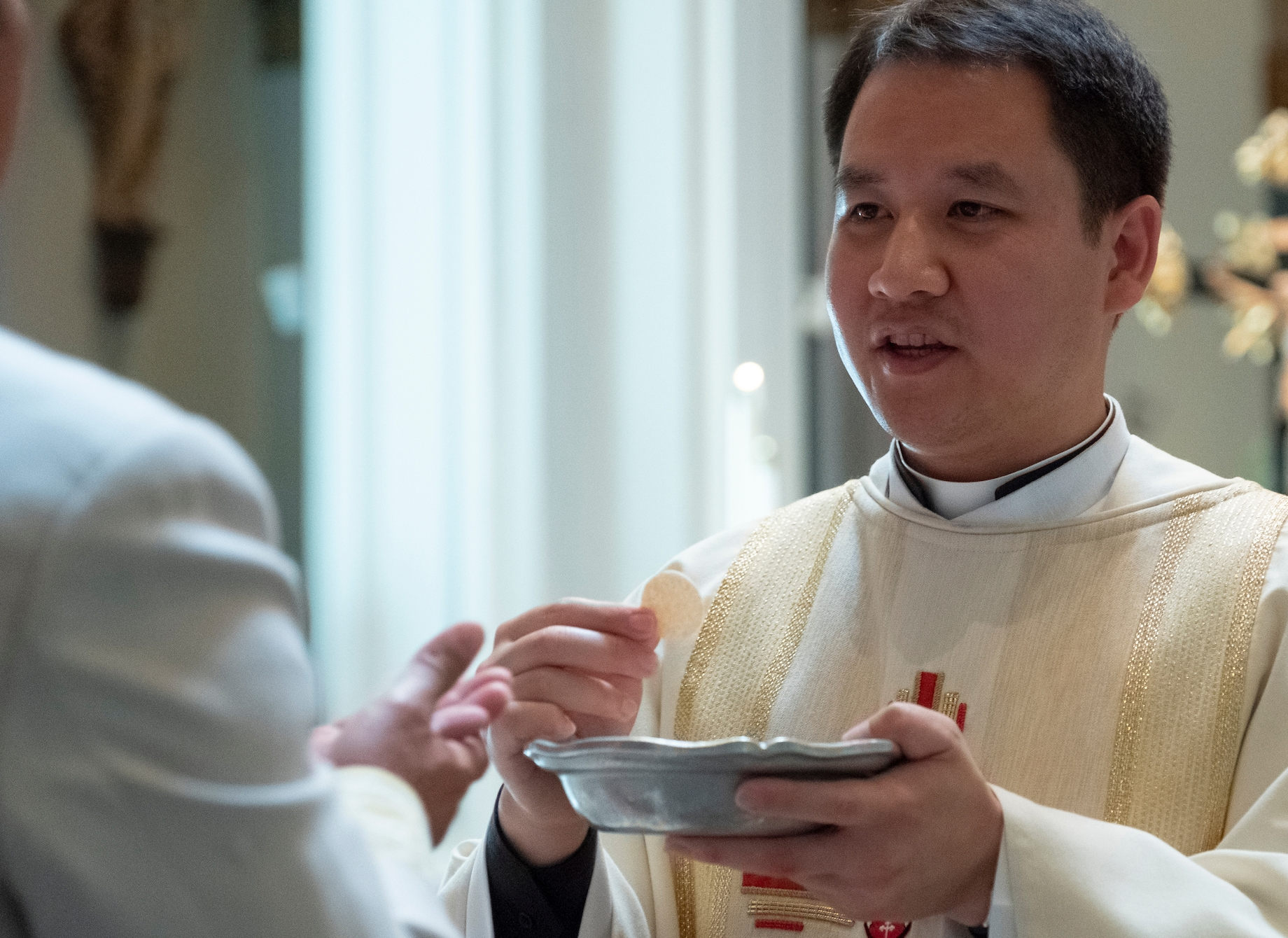 2018 Priesthood Ordination Mass for Anh Tran, Justin Ryan and Louis Cunningham at St. James Cathedral on Saturday June 9, 2018 in Seattle. (PHOTO by Stephen Brashear) Anh Tran distributing communion, eucharist